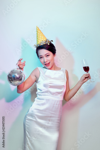 Portrait of a happy beautiful woman in white dress having a party and drinking champagne while standing with disco ball isolated over light background - 234475015