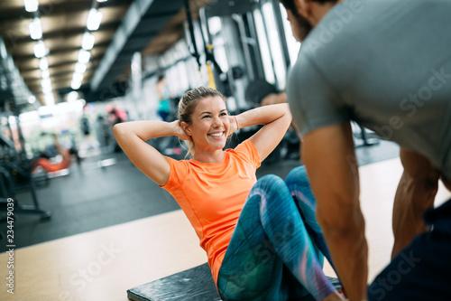 Leinwandbild Motiv Personal trainer helping young woman reach goals