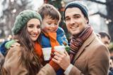 Family enjoying food and drink at Christmas market - 234482890