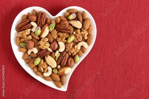 fototapeta na ścianę Nuts on a plate in the shape of a heart.