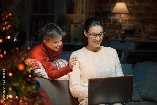 Leinwandbild Motiv Mother and son connecting with a laptop at Christmas