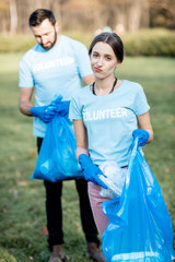 Portrait of a disappointed volunteers in blue t-shirts removing plastic rubbish in the park