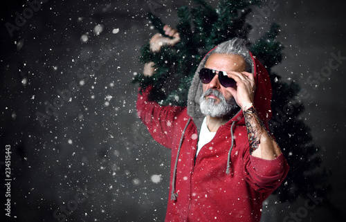 Leinwanddruck Bild Fashionable modern Santa old man in red fashion hoodie and sunglasses Merry Christmas