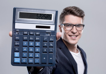 cheerful young handsome man looking at camera and holding calcul