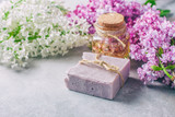 Handmade soap, Glass jar with fragrant oil and lilac flowers for spa and aromatherapy.