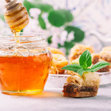 Honey, falling from a stick on a glass jar and traditional arabic dessert.