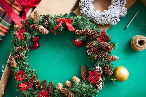 Boże Narodzenie z ręcznie robiony wianek iglasty ozdobiony czerwonymi kwiatami, kokardkami i szyszek