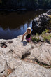 Blonde female hiker stands on a bluff cliff at Interstate State Park in Minnesota along the St. Croix River