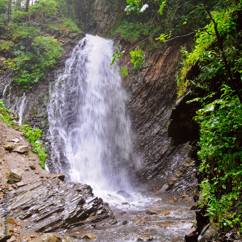 Leinwandbild Motiv Beautiful waterfall with trees, rocks and stones in forest. Ukrainian Carpathians.