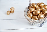 Golden eggs in a wicker basket on white wooden table background - 234567042