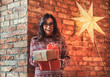 Leinwandbild Motiv Portrait of a cheerful brunette girl wearing glasses and a warm sweater holding gift boxes while leaning on a brick wall.