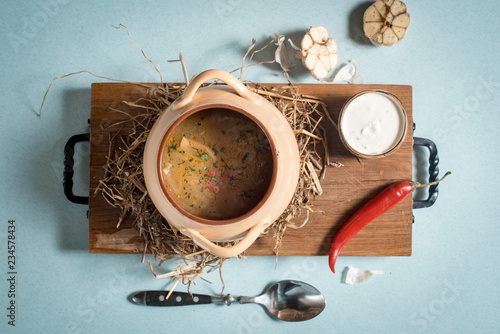 Meat stew with vegetables and herbs on old wooden table - 234578434