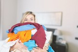 Young Tired Woman Carrying heap of different clothes