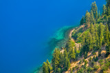Trees by intense blue water of Crater Lake - 234597473