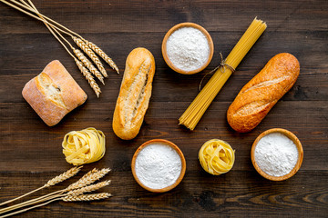 Homemade fresh bread and pasta near flour in bowl and wheat ears on dark wooden background top view