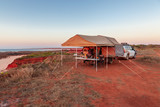 Man preparing a meal in Offroad camper trailer while camping on top of the red cliffs at James Price Point in the late afternoon in the Kimberley Region of Western Australia.