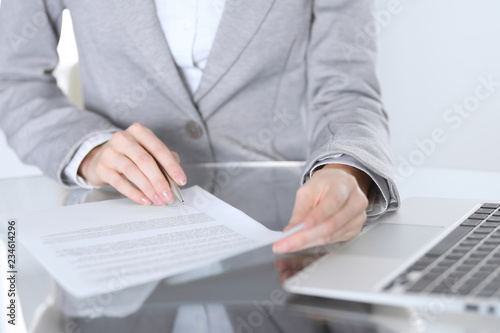 Close-up of female hands with pen over document,  business concept. Lawyer or business woman at work in office - 234614296
