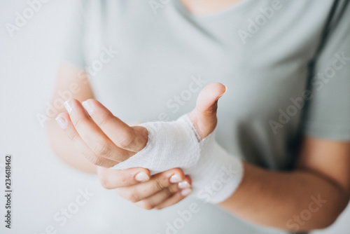 Leinwanddruck Bild Woman with gauze bandage wrapped around her hand