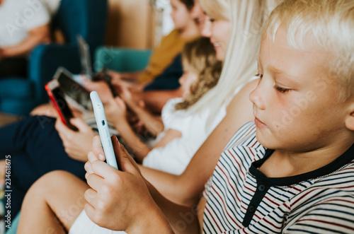 Leinwandbild Motiv Phone addicted family using their phones on the couch