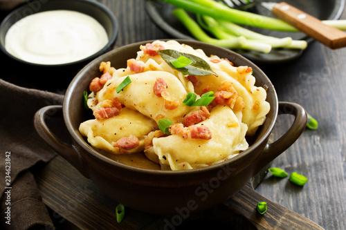 pierogi z ziemniakami w sosie cebulowo-bekonowym. Varenyky, vareniki, pierogi, pyrohy.