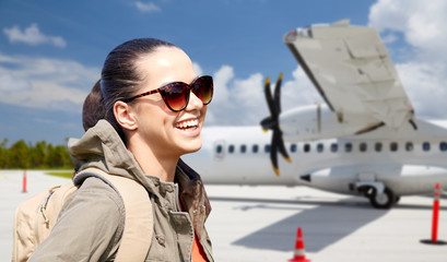 travel, tourism and people concept - smiling young woman in sunglasses with backpack over plane on airfield background