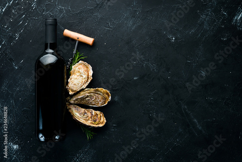 Leinwandbild Motiv Fresh oysters with ice and red wine. Seafood. Top view. Free copy space.