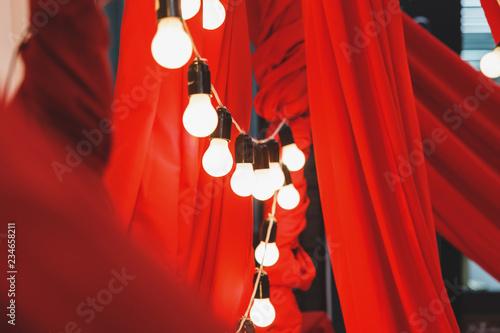 fototapeta na ścianę Beautiful light bulbs and red fabric. Photo Zone. Wedding or birthday. Concept