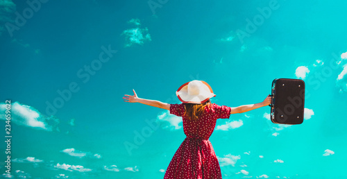 Leinwanddruck Bild young girl in a hat and red dress with open arms holds a suitcase against the blue sky background