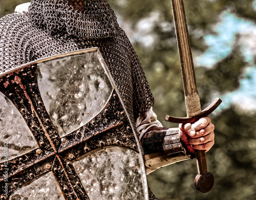 Closeup view on traditional medieval knight with shield and sword.
