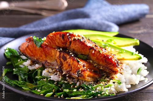 Leinwandbild Motiv Salmon teriyaki rice bowl with spinach and avocado.