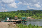 River ferry transports timber. Deforestation in Siberia. - 234672818