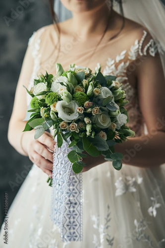bouquet in hands of the bride, woman getting ready before wedding ceremony - 234689691
