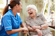 Leinwandbild Motiv Senior Woman Sitting In Chair And Laughing With Nurse In Retirement Home