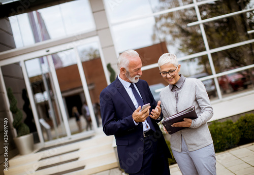 fototapeta na ścianę Senior business people talking outdoors and discussing a document outdoor