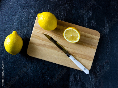 fresh lemon on a wooden cutting board - 234707687