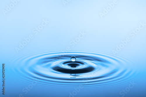 Leinwandbild Motiv Wassertropfen über blauer Wasseroberfläche