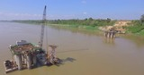 aerial panning shot of the bridge foundation and a barge mounted crane  in river - 234729810