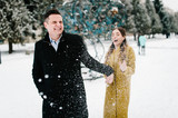Happy couple enjoying snowfall, hugging and laughing near christmas tree, outdoors in winter. Man and woman, season, love and leisure concept. - 234746426