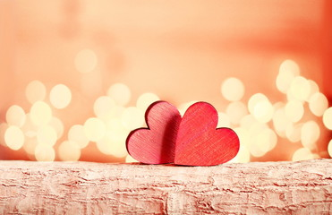 Hearts on a wooden branch and background is a bokeh.