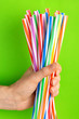 Leinwandbild Motiv Woman is holding colorful plastic straws in hand
