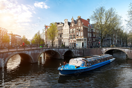 Amsterdam canal cruise ship with Netherlands traditional house in Amsterdam, Netherlands.