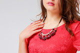 Original necklace on young woman in red elegant dress, close up,