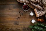 Hot beverage for warm winter evening. Mulled wine near cinnamon, fir branches, wool blanket, candles on dark wooden wooden background top view space for text - 234823254