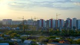 tower cranes on buliding site in modern city against sunset  - 234826875