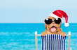 Leinwandbild Motiv Happy puppy with red christmas hat and sunglasses in a deck chair. Empty space for text