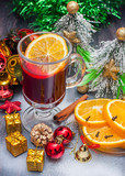Hot wine (mulled wine) with spices on wooden background.