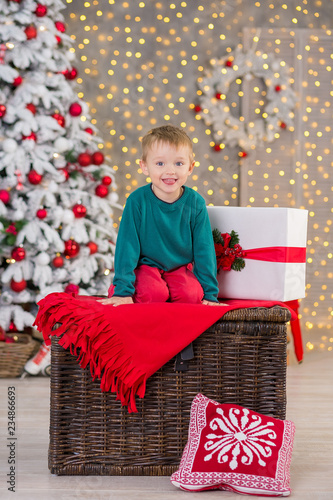 Christmas family child boy posing on wooden box close to presents and white fancy new year tree wearing red and green clothes.
