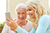 family, generation and people concept - happy smiling young daughter and senior mother with smartphone outdoors