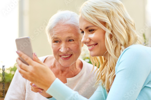 Leinwanddruck Bild family, generation and people concept - happy smiling young daughter and senior mother with smartphone outdoors