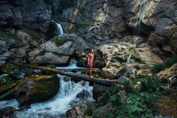 girl walking through a tree in a red dress on the background of a waterfall